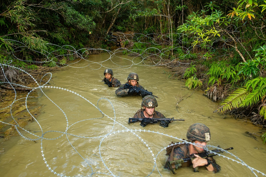 U.S. Marines with 1st Battalion, 2nd Marine Regiment (V12), 3d Marine Division, guides their fellow Marine during a pulley system during the Infantry Jungle Skills Course (IJSC) at the Jungle Warfare Training Center on Camp Gonsalves, Okinawa, Japan, September 17th, 2020.