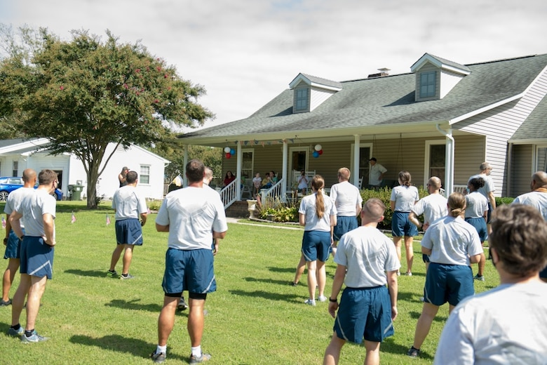 Airmen wearing their physical fitness uniforms stand facing a home