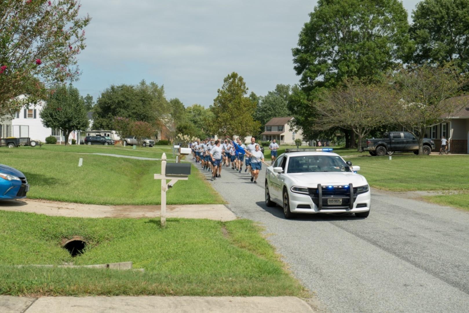 A law enforcement patrol vehicle escorts Airmen as they run through a neighborhood