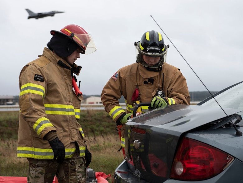 U.S. Air Force Staff Sgt. Harley Lovehall, left, and Airman 1st Class Forrest Rennaker, 52nd Civil Engineer Squadron Fire and Emergency Services firefighters, aid in a demonstration of a vehicle extrication for 52nd Fighter Wing leadership by removing the trunk of a vehicle Oct. 5, 2020, at Spangdahlem Air Base, Germany. Lovehall and Rennaker, along with other 52nd FES Airmen, attended the demonstration to help 52nd Wing leadership and answer any questions during the process. (U.S. Air Force photo by Senior Airman Melody W. Howley)