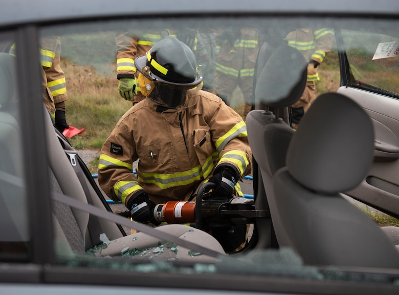 52nd Fighter Wing leadership participate in a vehicle extrication simulation for Fire Prevention Week, Oct. 5, 2020, at Spangdahlem Air Base, Germany. Wing leadership had the opportunity to use tools and simulate rescuing a victim from a vehicle. (U.S. Air Force photo by Senior Airman Melody W. Howley)