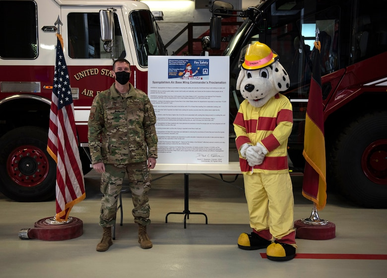 U.S. Air Force Col. David Epperson, 52nd Fighter Wing commander, and Sparky, the fire dog, pose for a photo after the signing of the Spangdahlem Air Base Wing Commander's Proclamation, Oct. 5, 2020, at Spangdahlem AB, Germany. The Wing Commander's Proclamation ensures Saber families will take necessary measures to prevent home fires and continue to educate themselves on fire prevention safety measures. (U.S. Air Force photo by Senior Airman Melody W. Howley)