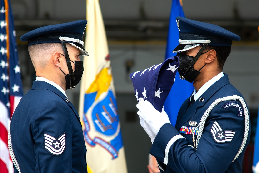 A photo of Tech. Sgt. Jonathan D. Kane and Staff Sgt. William L. Caldwell folding an American flag.