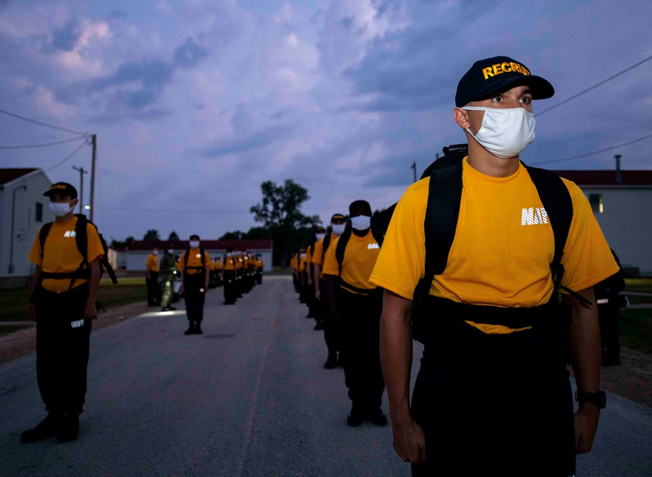 Navy recruits wearing face mask stand in formation.