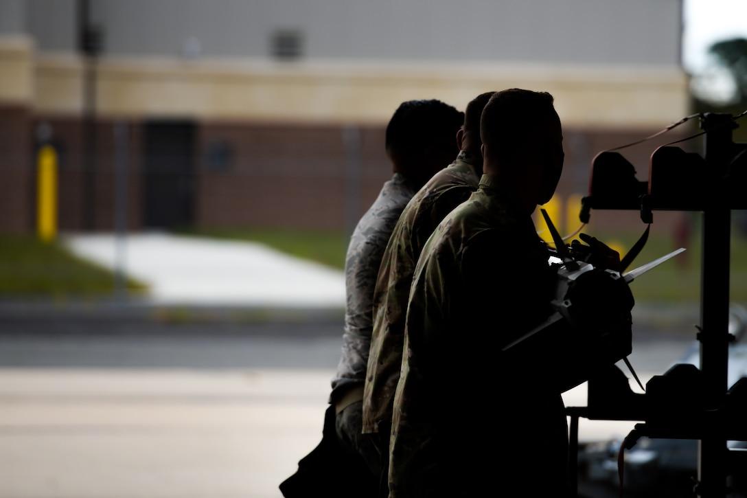 A photo of Senior Airman Herys F. Rivera, Staff Sgt. Andrew K. Finnegan and Senior Airman Connor M. Jarvie loading an AIM-54 Phoenix onto an F-16C Fighting Falcon.