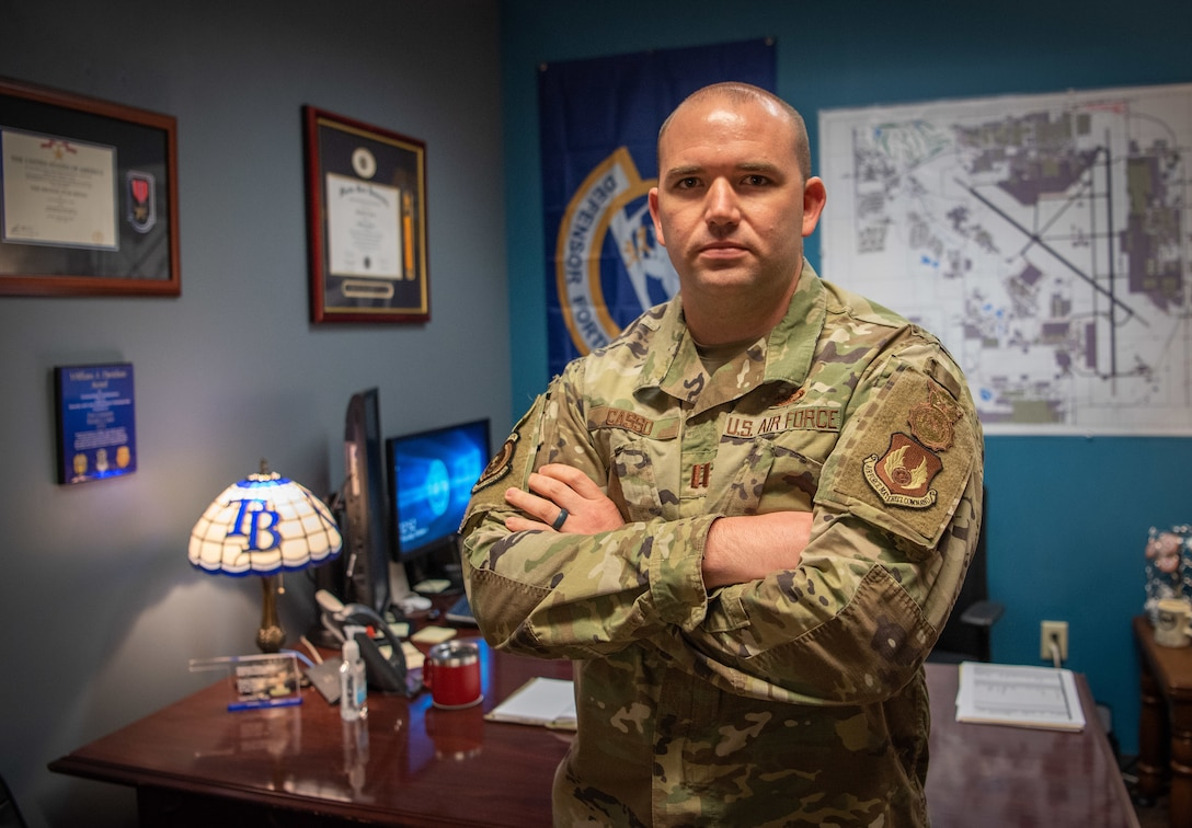 Airman with arms crossed standing in front of his desk.