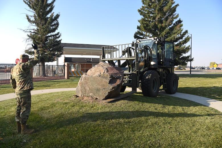 airmen loading memorial stone on forklift