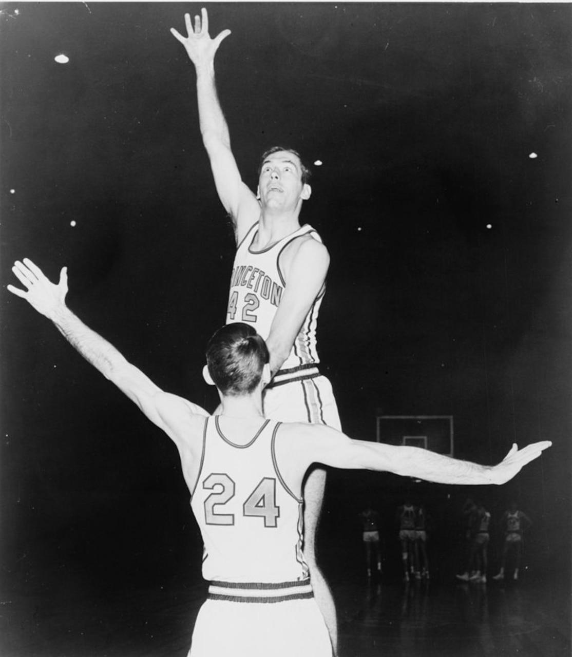 Men play basketball in a gymnasium.