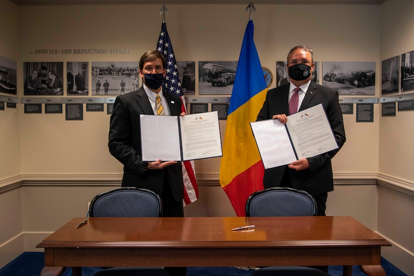 Two men stand in front of flags holding documents.