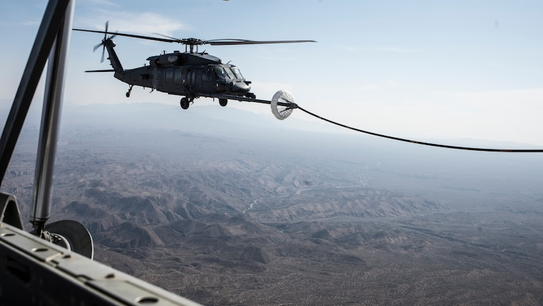 A photo of a helicopter performing air-to-air refueling