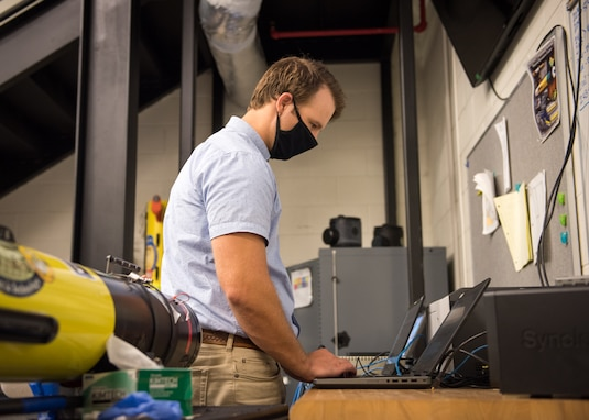 Adam Coffman, NSWC PCD computer engineer, performs cyber reconnaissance of the unmanned system. U.S. Navy photo by Anthony Powers