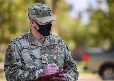 U.S. Air Force Col. Ryan Nye judges a car show.