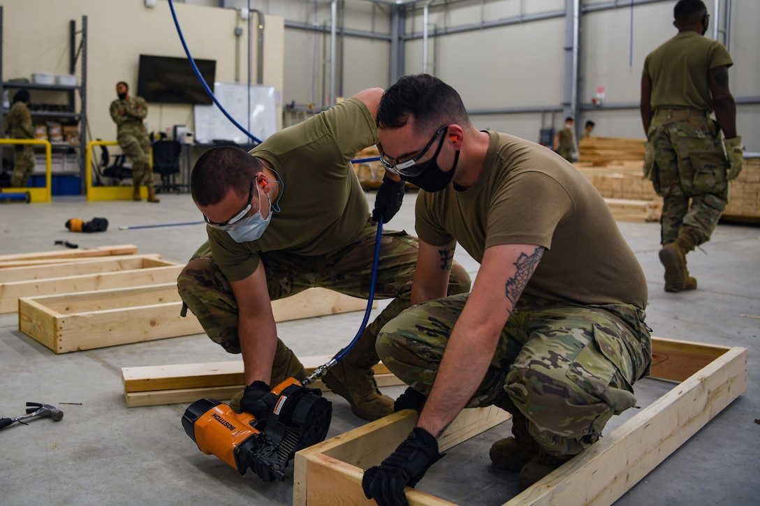 Airmen with the 731st Munitions Squadron build bracing for munitions during Waking Giant at Camp Darby, Italy, Oct. 7, 2020. The bracing was meant to keep munitions in place while being shipped inside an intermodal shipping container. (U.S. Air Force photo by Airman 1st Class Thomas S. Keisler IV)