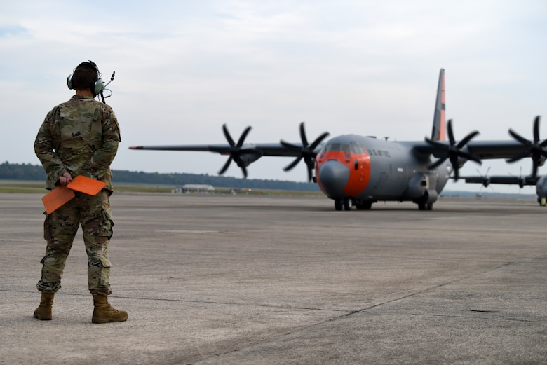 Airman stands with marshaling flags behind back ready to direct plane