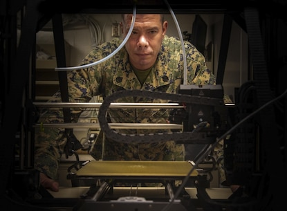 PHILIPPINE SEA (Aug. 24, 2020) Staff Sgt. Jack Hubbard, a radio technician with Combat Logistics Battalion 31, 31st Marine Expeditionary Unit (MEU), observes a 3D printer as it prints an equipment part used aboard USS New Orleans (LPD 18).