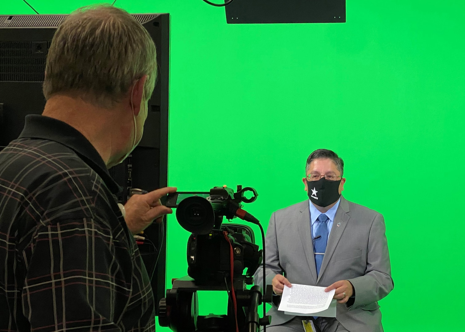 A customer account manager for DLA Disposition Services in Battle Creek, Michigan sits in front of a green screen in a TV studio.