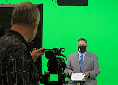 Joe Cavazos, a customer account manager for DLA Disposition Services in Battle Creek, Michigan sits in front of a green screen in a TV studio.