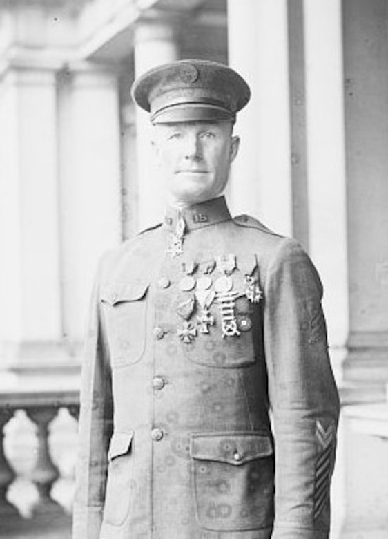 A man in military uniform stands amid pillars.