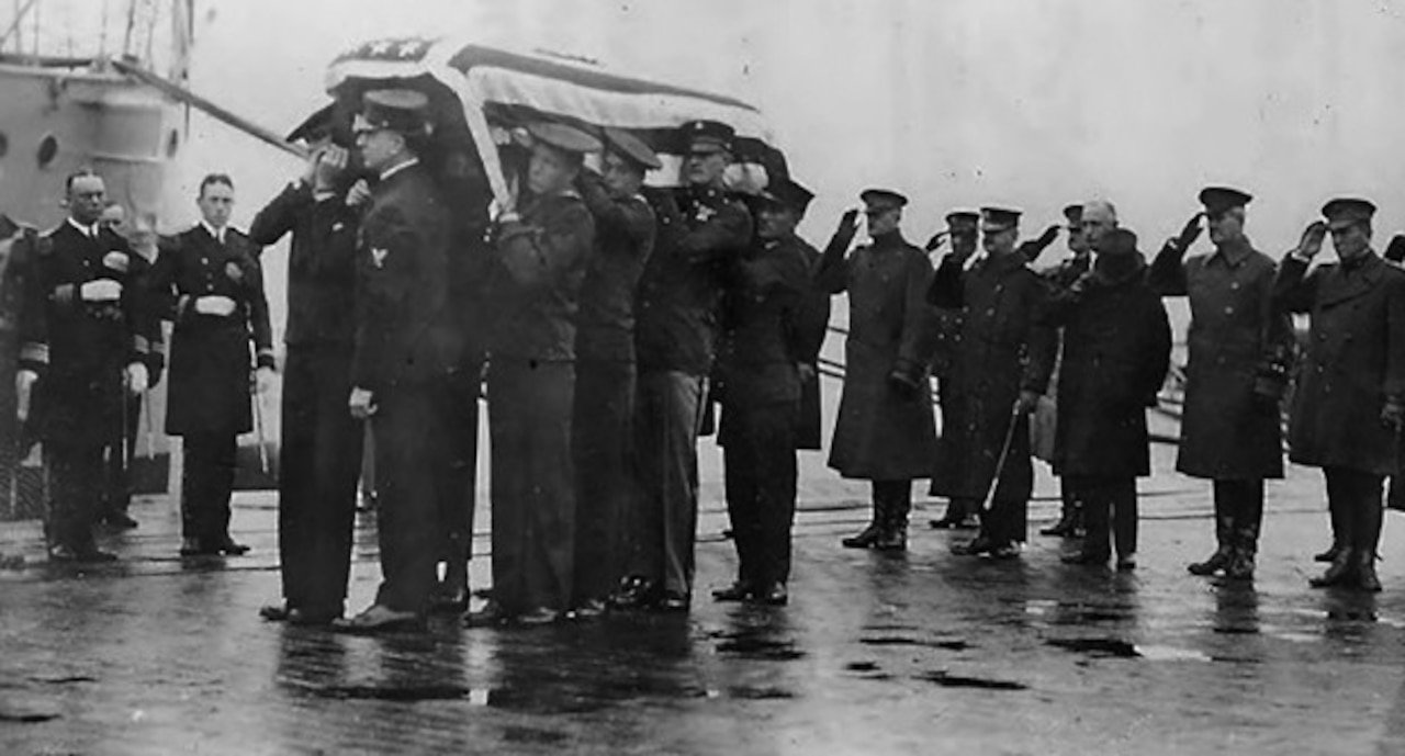 Several men salute as others carry a casket draped in an American flag.