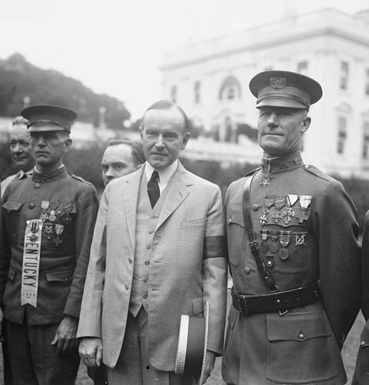 Two soldiers stand beside another man outside.