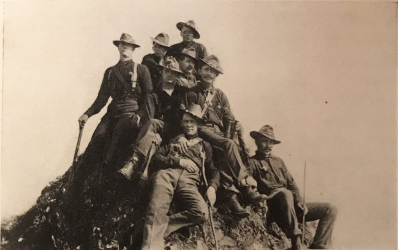 Eight men sit together on the top of a dirt mound.