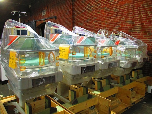 Five infant hospital beds are packaged in a warehouse awaiting delivery.
