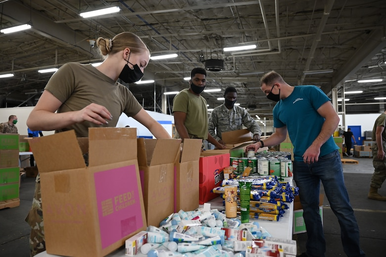 Volunteers along with local community members assemble boxes of food and personal care items.