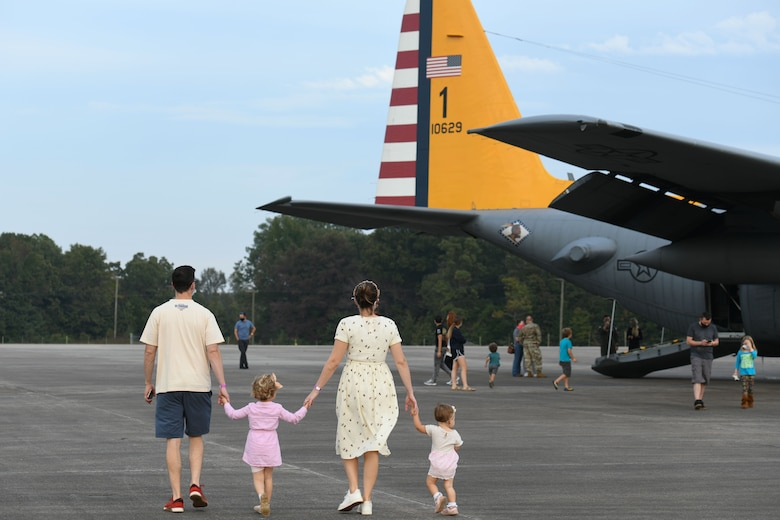 A Family of 4 walks holding hands towards a C-130 plane