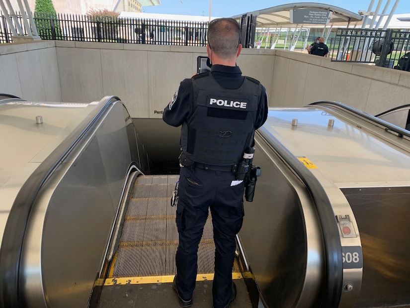 A Pentagon police, shown from behind, stands and holds up a tablet at the top of an escalator.