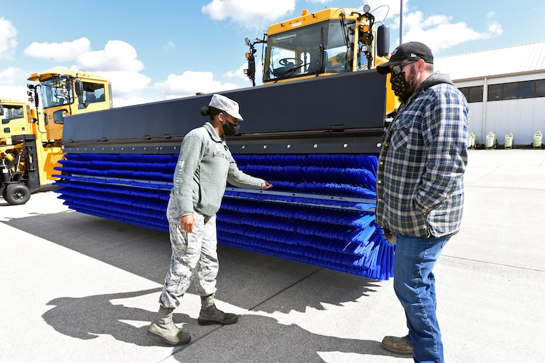 U.S. Air Force Senior Airman Royalty Jones-Gavin, command support, 88th Air Base Wing, inspects an Oshkosh airfield snow broom with heavy equipment operator Dustin McIver, 88th Air Base Wing Civil Engineer Group, before test driving the big machine at Wright-Patterson Air Force Base on Oct. 2, 2020. CEG drivers paraded the snow removal equipment across the airfield for review by 88 ABW Commander Col. Patrick Miller and local news reporters to demonstrate the equipment needed to keep the base and the airfield operational. (U.S. Air Force photo by Ty Greenlees)