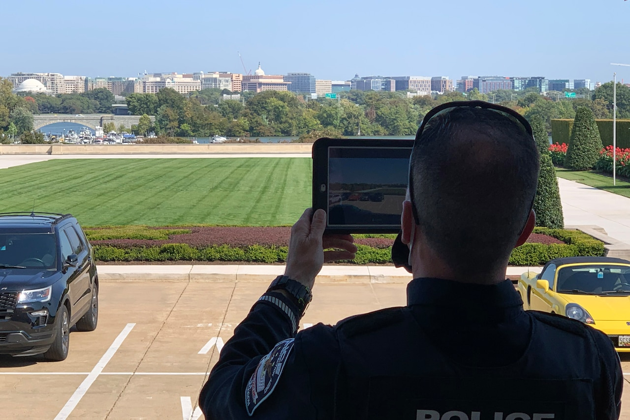 A Pentagon Force Protection Agency officer holds up a tablet while standing with a view of the Washington, D.C., skyline.