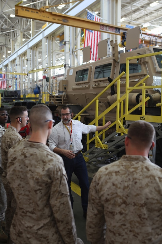 Several men in military uniforms listen as a man in civilian clothes speaks.  A military vehicle is on an assembly line behind the men.