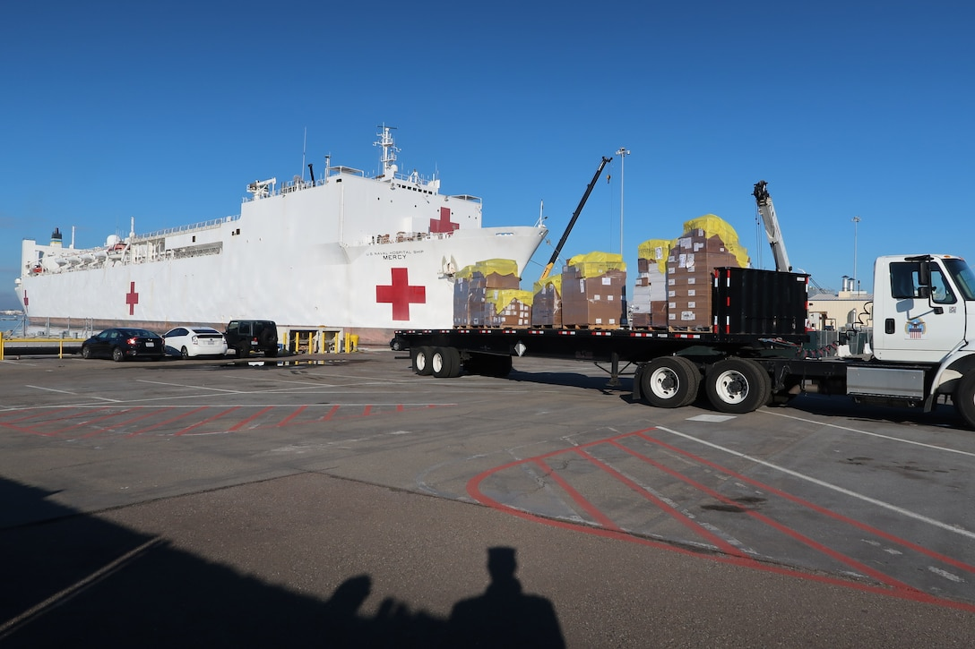 A truck loaded with pallets waits on a concrete lot. Nearby, a naval vessel bearing a red cross is docked.