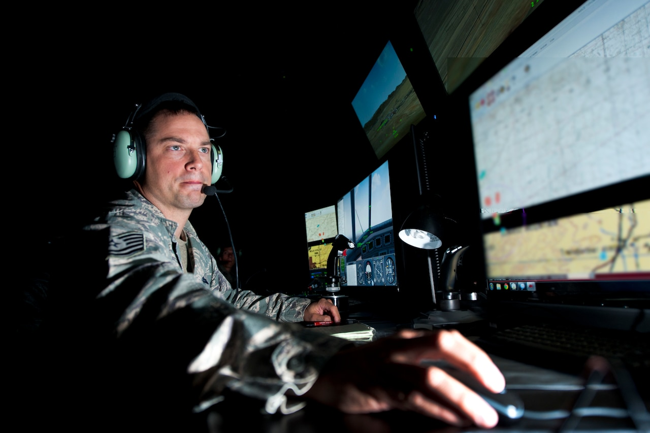 A man in military uniform wears a headset in a room lit only by computer screens.