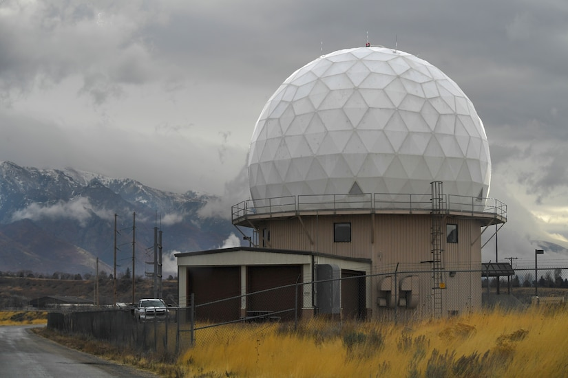 A golf ball-shaped building sits inside a fenced area with mountains in the background.