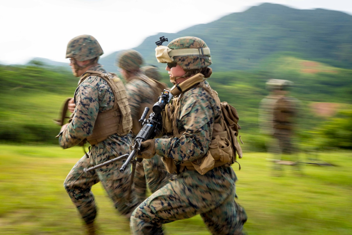 Marines run together while holding their weapons.