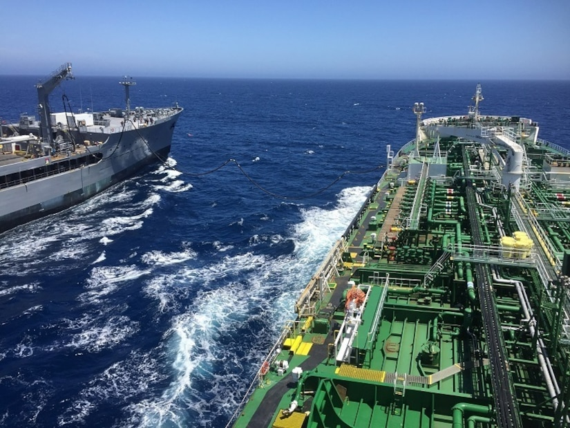 Two ships side by side perform a consolidated cargo replenishment-at-sea