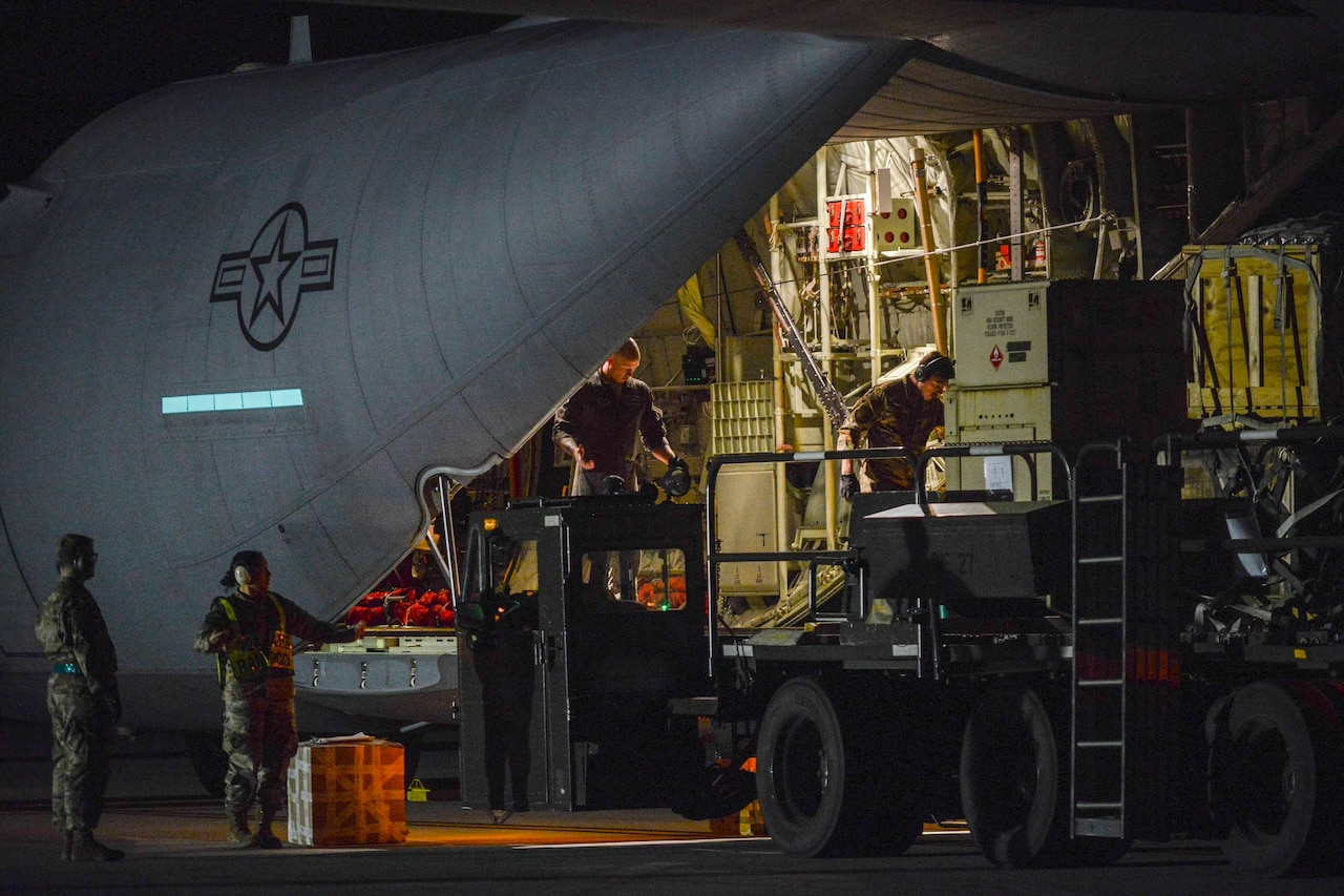 Two service members stand inside the cargo hold at the rear of an airplane, while one loads some pallets onto machinery. Two other service members stand outside the plane; a large box sits next to them.