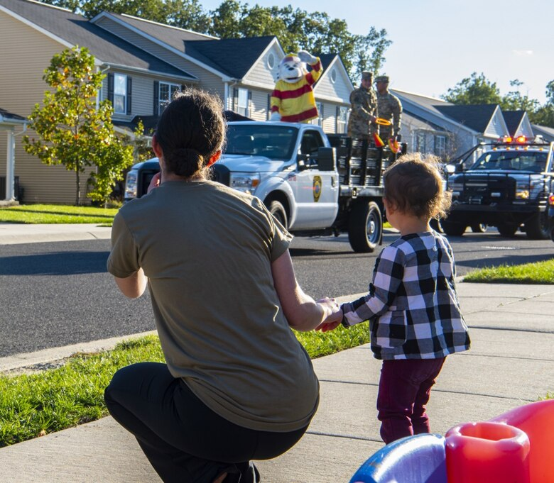 A mother and child wave to members of the 87th Civil Engineering Group during a fire prevention awareness parade on Oct. 8, 2020 at Joint Base McGuire-Dix-Lakehurst, New Jersey. Fire Prevention Week begins October 4 and runs until October 10. The goal of Fire Prevention Week is to raise fire safety awareness. (U.S. Air Force photo by Airman 1st Class Matt Porter)