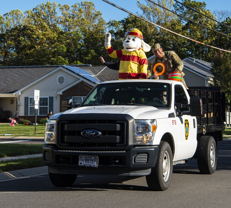 Sparky the Fire Dog and firefighters from the 87th Civil Engineering Group waves during a fire prevention awareness parade on Oct. 8, 2020 on Joint Base McGuire-Dix-Lakehurst, New Jersey. Fire Prevention Week begins October 4 and runs until October 10. The goal of Fire Prevention Week is to raise fire safety awareness. (U.S. Air Force photo by Airman 1st Class Matt Porter)