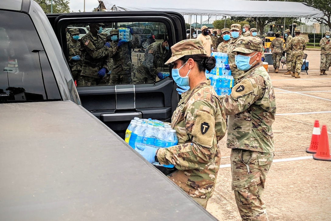 Two soldiers car bottled water into a vehicle.