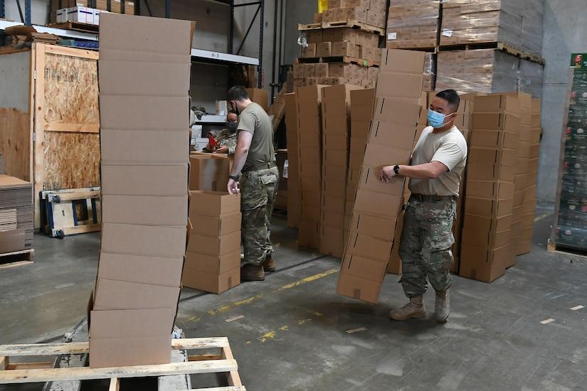 Airmen wearing masks carrying boxes.
