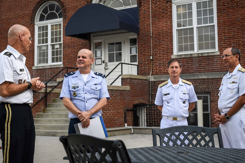 Four men wearing uniforms stand outside a building; two of the men are talking.