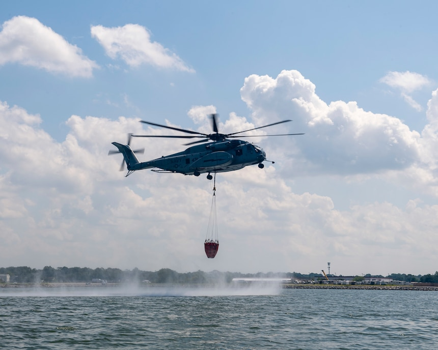 """An MH-53E Sea Dragon helicopter, assigned to the """"Sea Dragons"""" of Helicopter Mine Countermeasures Squadron (HM) 12, performs aerial firefighting training exercises using a 1,300 gallon Bambi Bucket Sept. 3, 2020."""