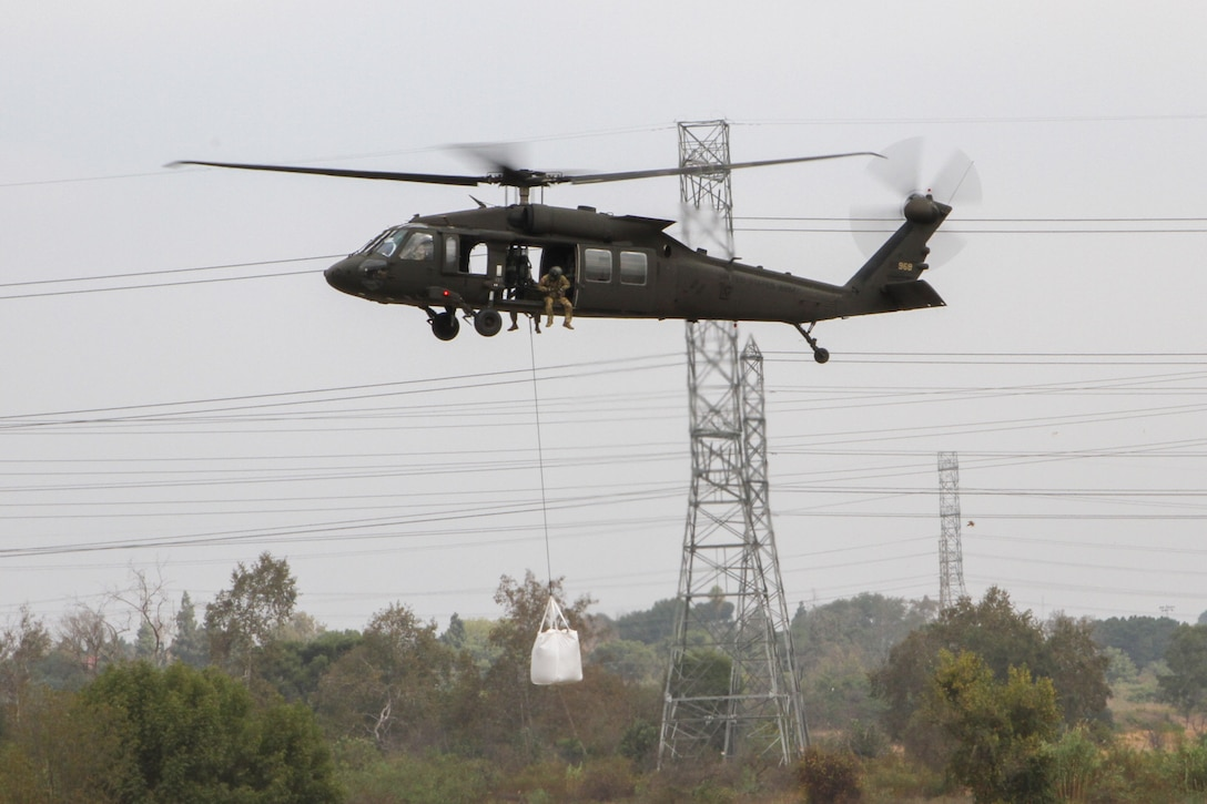 A California Army National Guard UH-60 Black Hawk places a 3,000-pound sandbag at the Whittier Narrows Dam Basin in Montebello, California, as part of an exercise during which the district teamed up with the California Army National Guard to demonstrate flood-mitigation capabilities.