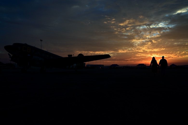 A couple walks behind a heritage Aircraft at sunset