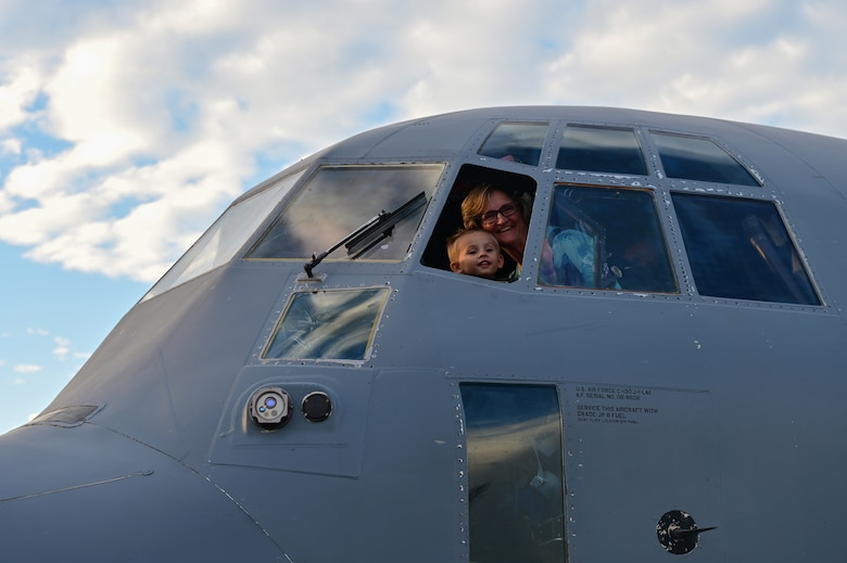 And elderly woman and child look out the window of a C-130