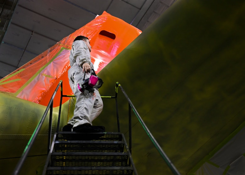 An Airman in a white suit speaks with another Airman on a set of stairs next to a C-130J.