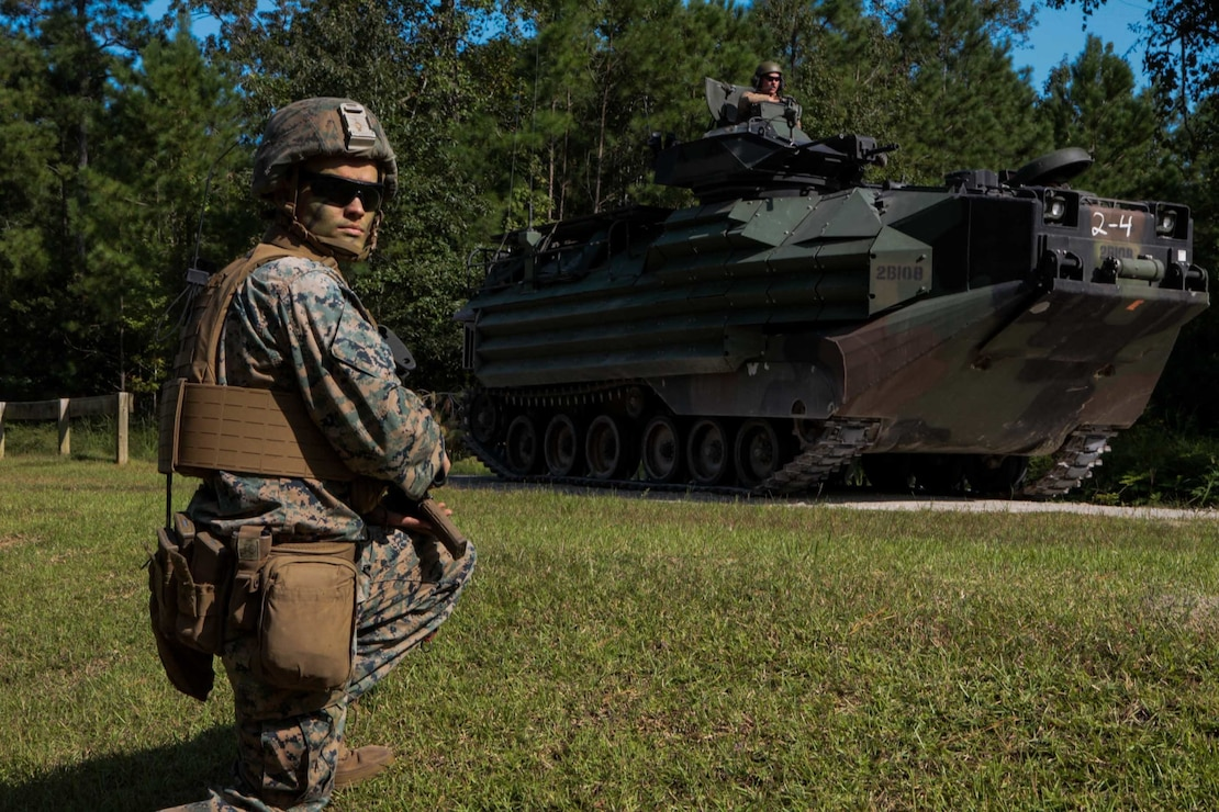 U.S. Marine Corps Lance Cpl. Alexander Dawson, a mortarman with 1st Battalion 8th Marines, provides security next to an amphibious assault vehicle at the area of operation at Camp Lejeune, N.C., Sept. 22, 2020. The purpose of the exercise was to promote familiarization with ship to shore procedures and raid tactics for pre-deployment readiness with the 24th Marine Expeditionary Unit. (U.S. Marine Corps photo by Lance Cpl. Davis Harris)