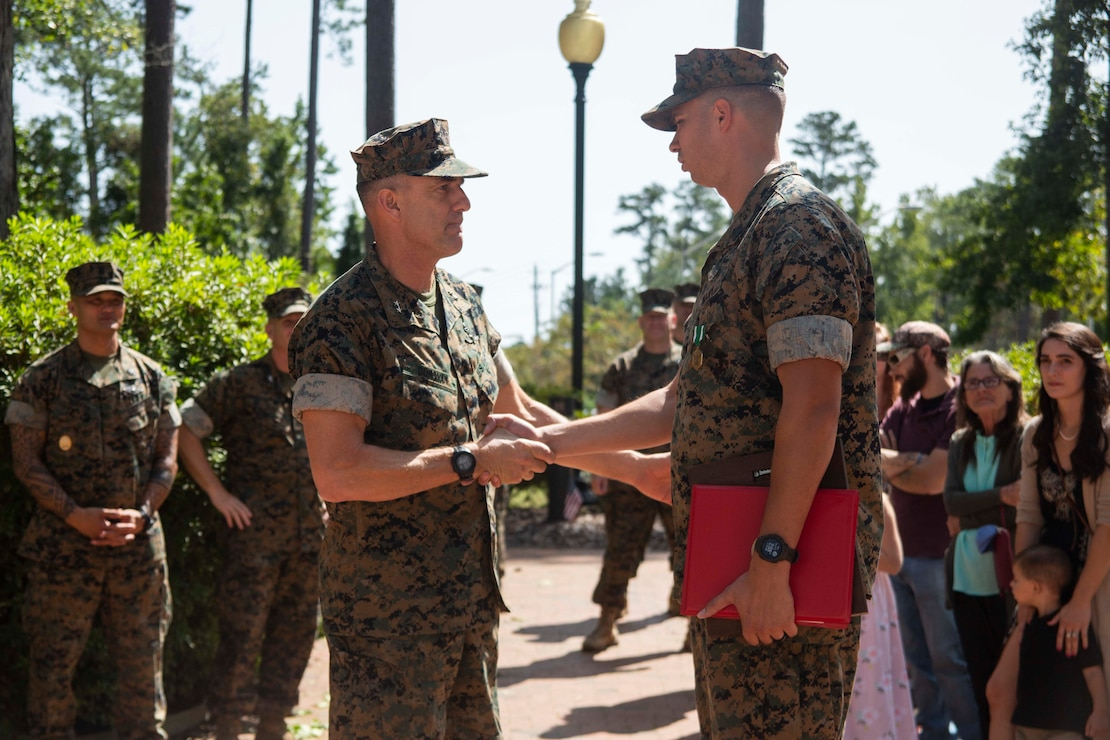 """Major Gen. Francis Donovan, 2nd Marine Division commanding general, congratulates HM1 Michael D. Bryson on his achievements during an award ceremony at Camp Lejeune, N.C., September 22, 2020. Bryson received the Chief Hospital Corpsman George William """"Doc"""" Piercy award, which recognizes one Navy corpsmen who has earned the Fleet Marine Force (FMF) badge for contributing to the combat readiness of any air or ground element in the Marine Corps. Bryson also received a Navy Commendation Medal for his outstanding service and accomplishments while serving as a corpsman for 1st Battalion 8th Marine Regiment. (U.S. Marine Corps photo by Lance Cpl. Nicholas Guevara)"""